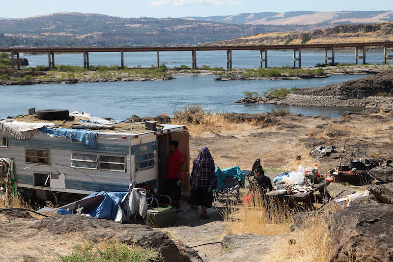 This photo taken on August 22, 2014 at Lone Pine, a Native American fishing site on the Columbia River near The Dalles, shows the home of Ranetta Spino and her family at the river's edge. Lone Pine is one of 31 fishing sites developed as a replacement for tribal fishing grounds flooded or destroyed by hydroelectric dams. About 40 people, including children, permanently live at the fishing site in substandard conditions. (AP/Gosia Wozniacka)