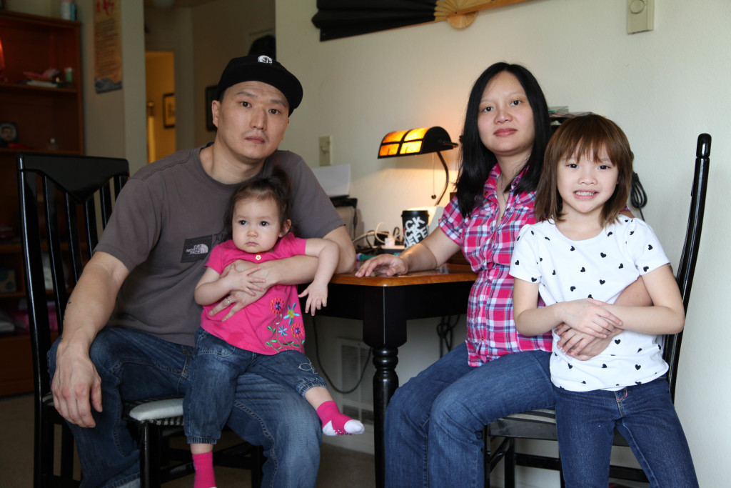 In this photo taken on Thursday, March 19, 2015, Korean adoptee Adam Crapser poses with his daughters, 1-year-old Christal and 5-year-old Christina, and his wife Anh Nguyen in the family's living room in Vancouver, Wash. Crapser, whose adoptive parents neglected to make him a U.S. citizen, will face an immigration judge in April and could be separated from his family and deported to South Korea, a country he does not know. (AP Photo/Gosia Wozniacka)