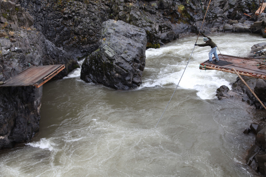 In this photo taken on October 20, 2014 on the Klickitat River, a tributary of the Columbia River near Lyle, Washington, a Native American fisherman catches fish on a platform. Platform fishing is one of the most common Native American fishing techniques on the rivers in the Columbia Basin. For millennia, Indians have fished and lived along the ColumbiaÕs shores, the salmon central to their culture and religion, sustenance and trade. (AP/Gosia Wozniacka)